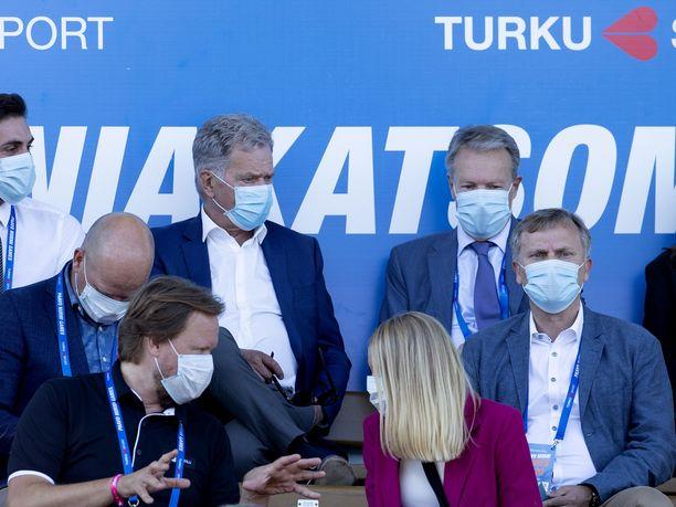 Presidentti Sauli Niinistö ja poliitikko Ilkka Kanerva istuvat Paavo Nurmen stadionilla kasvomaskeihin suojautuneina.