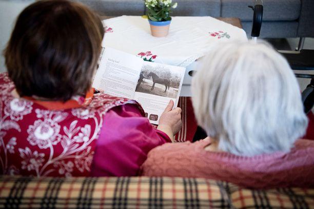Levollinen hetki keskellä päivää: hoitaja lukee ääneen asukkaalle mieluista kirjaa.