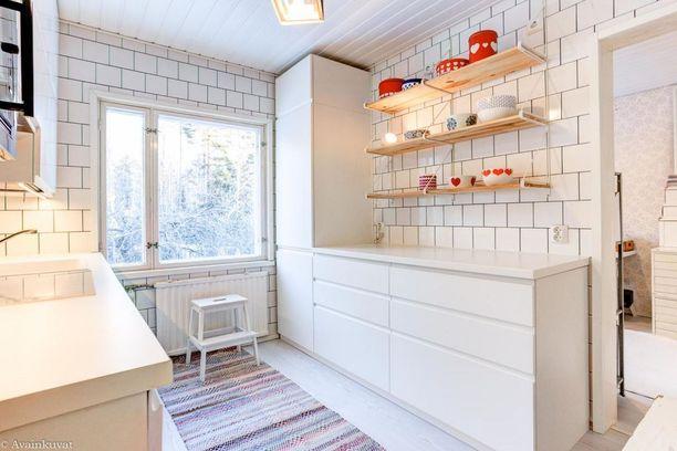 Rintamamiestalon keittiön kattoon asti ulottuva laatoitus näyttää sekä raikkaalta että helpottaa seinäpintojen puhtaanapitoa. Lisätilaa tulee avohyllyistä.