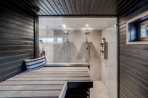 Lasiseinä tuo valon sisään tummanpuhuvaan saunaan. Tässäkin saunassa lauteet ja seinät ovat eri väriset.