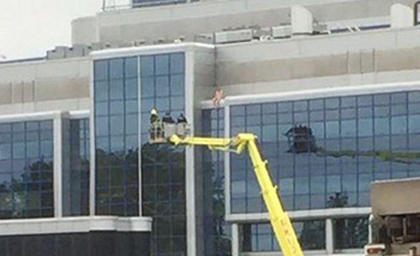 Silminnäkijä kertoo Iltalehdelle, että alastomalta näyttävä ihminen on hallintorakennuksen päällä istumassa.