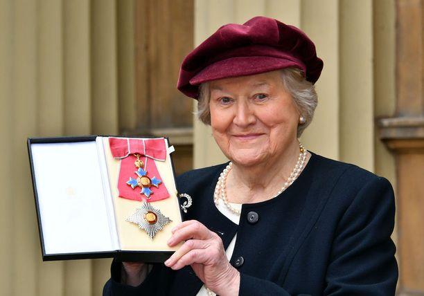 Dame Patricia Routledge esittelee prinssiltä saamaansa mitalia.