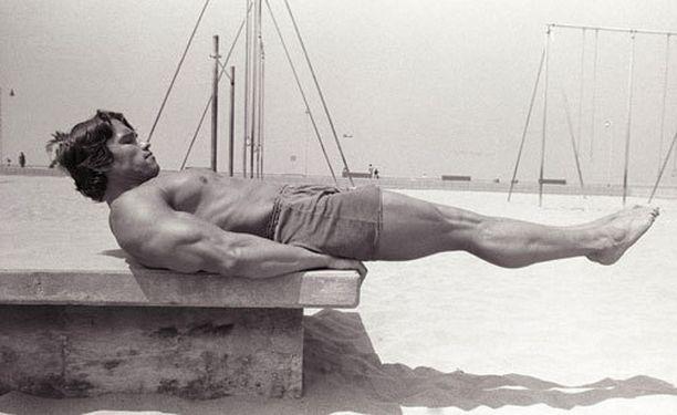 Arnold Schwarzenegger näyttää mallia vatsalihastreenistä.