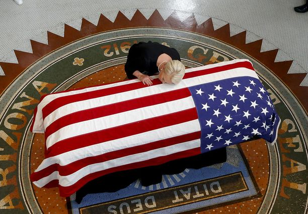 Cyndi McCain kumartui suutelemaan aviomiehensä arkkua.