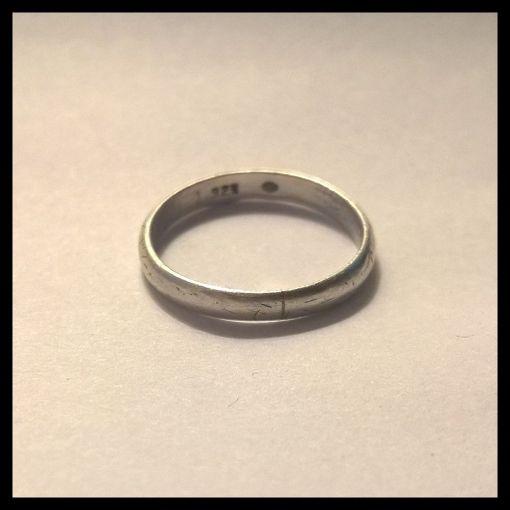Yksi sormuksista on kapea ja hopeinen. Sen sisälle tehty kaiverrus on vanhanaikaisesti tyylitelty.