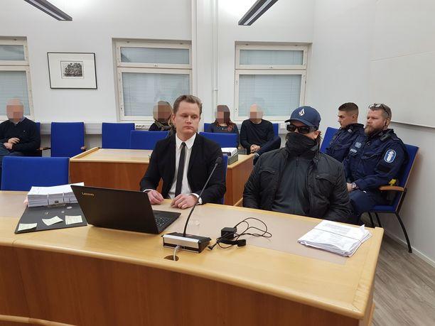 Murhasta syytetty mies pukeutui oikeudenkäynnin alussa kasvot peittävään huiviin ja aurinkolaseihin.