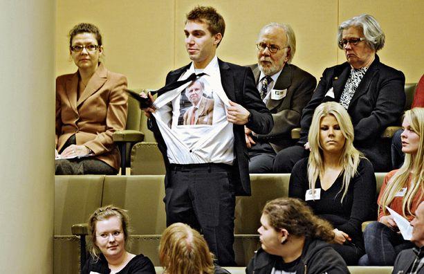 HÄIRIKÖI Näyttelijä Jarkko Niemi repi kauluspaitansa kesken eduskunnan kyselytunnin. Eduskunnan vahtimestari saattelivat näyttelijän nopeasti ulos.