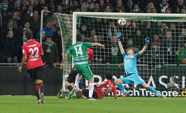 Frankfurtin maalivahti Lukas Hradecky paikkaa virheensä torjumalla Claudio Pizarron laukauksen.