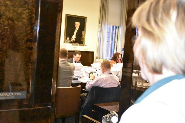Järkälemäiset paperipinot symboloivat sote-uudistuksen käsittelyn tilaa ajan valuessa vaalikauden tiimalasissa kohti loppuaan. Kokoomuksen kansanedustaja ja perustuslakivaliokunnan jäsen Wille Rydman (takana keskellä) on julkaissut kolumnin, jossa hän kirjoittaa, että perustuslain kirjaimen yli ei saisi valiokunnassa kävellä sote-uudistuksen hyväksymisen nimissä. Kokoushuoneeseen on astumassa RKP:n puheenjohtaja Anna-Maja Henriksson.
