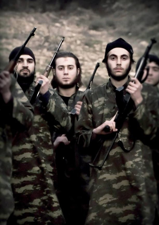 Isisin militantit poseeraavat propagandavalokuvassa aseineen Syyrian Raqqassa.