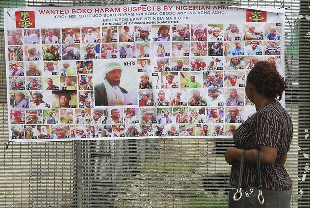 Nainen katseli Boko Haram -terroristijärjestön etsintäkuulutettujen kuvia Nigerian Bayelsassa. Arkistokuva.