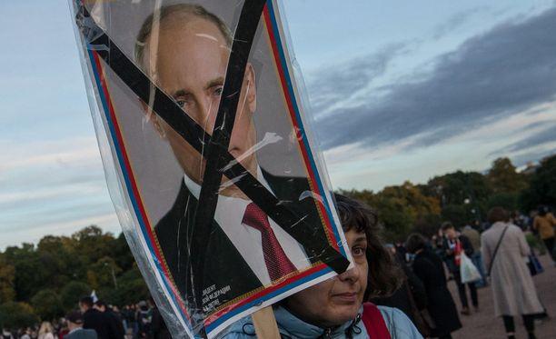 Nainen Putinia vastustavassa mielenosoituksessa. Arkistokuva.