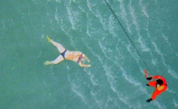 Pelastustyöntekijä laskeutuu kohti meressä kelluvaa uhria. Kuvakaappaus uutislähetyksestä.