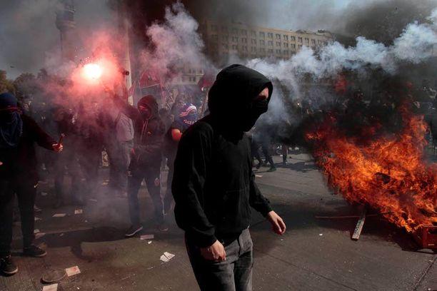 Mielenosoittajat sytyttivät soihtuja presidentin La Moneda -palatsin läheisyydessä Santiagossa.