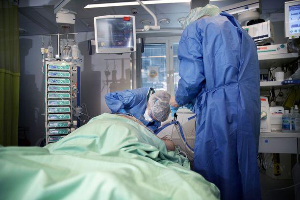 Hoitohenkilökunta varmistaa hengitysputken asentoa ja helpottaa potilaan kasvoihin kohdistuvaa painetta Meilahden sairaalan korona-teholla.