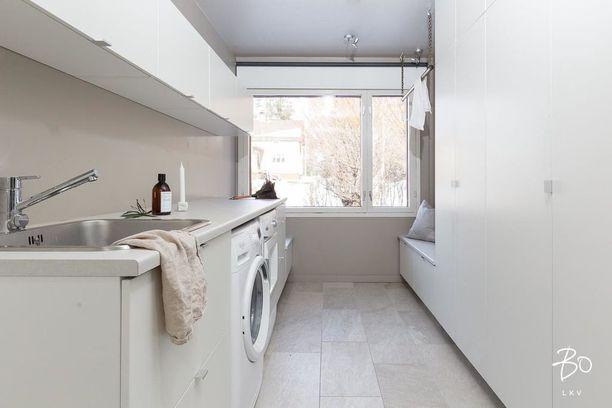 Riittävä kaappitila takaa, että kodinhoitohuone näyttää siistiltä. Tämän kodinhoitohuoneen erikoispiirteenä on matala kaappi, jonka päälle voi kotitöiden lomassa hetkeksi istahtaa.