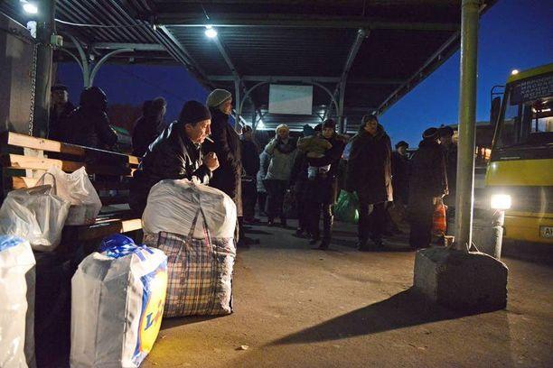 Ihmiset odottavat linja-autoasemalla mahdollisia vapaita paikkoja busseissa.
