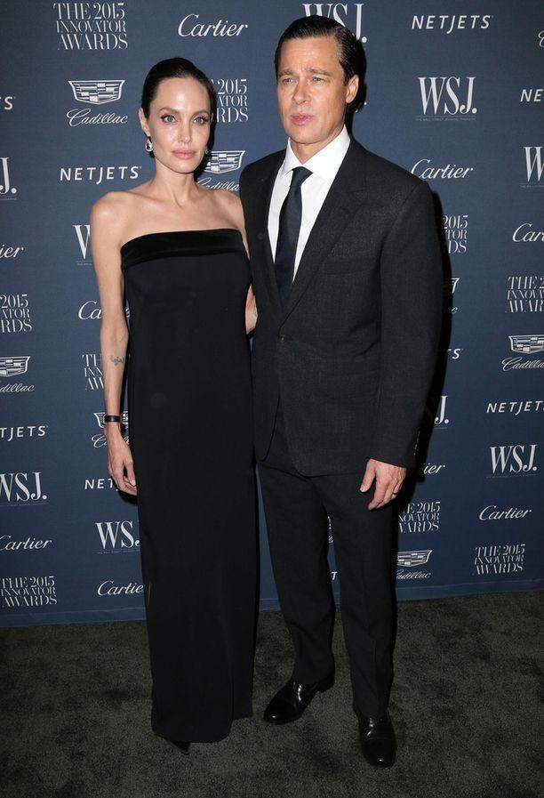 Angelina Jolie ja Brad Pitt tuiman näköisinä tummissa hiuksissa ja asuissa.
