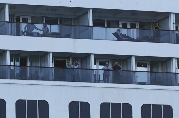 Zaandam-aluksen matkustajat näyttäytyivät hyttiensä parvekkeilla Panama Cityn edustalla perjantaina.
