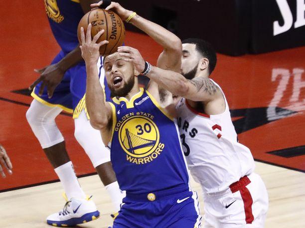 Golden State Warriorsin tähtipelaaja Stephen Curry vääntää pallosta Toronto Raptorsin Fred VanVleetin kanssa.