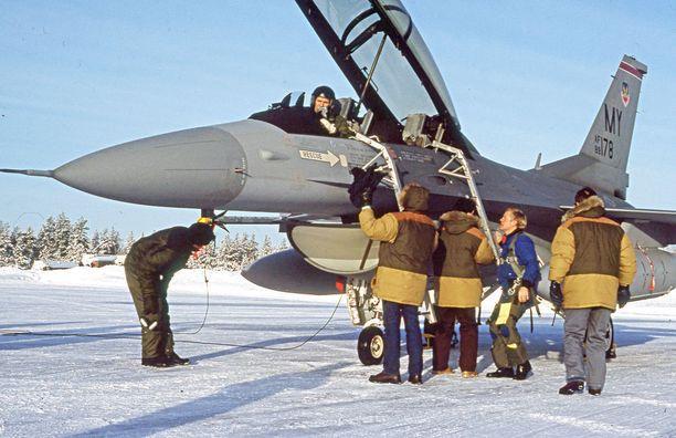 Pakkastesti. Ilmavoimat tutki neljä konetyyppiä kauttaaltaan. Kuvassa on amerikkalainen F-16D Kuoreveden Hallissa kylmänä pakkasaamuna 6. helmikuuta 1992. Ohjaamossa on koelentäjä majuri Pauli Perttula, maassa sinisessä puserossa General Dynamicsin koelentäjä Jon Beesley. Ruskeisiin talvipuseroihin pukeutuneet ovat amerikkalaisyhtiön mekaanikkoja ja ilmavoimien lämpöpuvussa kurkkiva mekaanikko on Ari Ikkala Koelentokeskuksesta. F-16D lensi tuona päivänä kolme koelentoa. Koneen varustuksena on kaksi lisäsäiliötä siivissä ja AIM-9 Sidewinder -ohjukset siiven kärjissä.