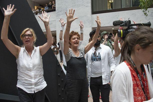 """Mielenosoittajien käsiin oli kirjoitettu """"We Care"""" eli """"me välitämme""""."""