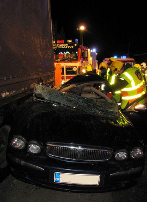 Musta Jaguar-merkkinen henkilöauto rusentui kolarissa pahasti.