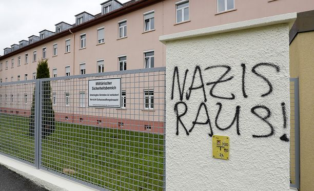 Natsit ulos. Mielenosoittajat ovat maalanneet iskulauseen kasarmin aidalle.