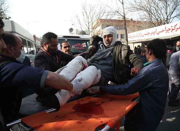 Ihmiset kantoivat pommi-iskussa haavoittunutta miestä tammikuun 27. päivänä Kabulissa. Itsemurhaiskussa kuoli ainakin 95 ihmistä.