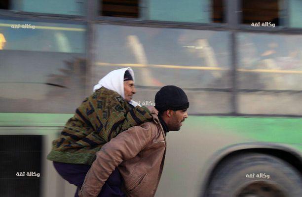 Mies kantoi vanhempaa siviiliä evakuointibussiin Itä-Aleppossa.