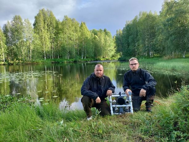 Arto Suanto (vas.) ja Antti Suanto kuvattuna vanhempiensa kotipaikan rannassa pienoissukellusveneen kanssa.