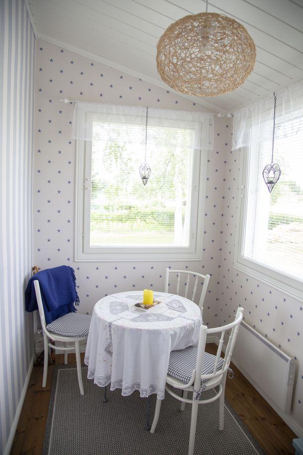 Pienelle verannalle mahtuvat pöytä ja kolme tuolia. Lisäksi siellä ovat kenkäteline ja naulakko.