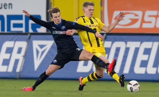 Paderbornin Roope Riski pysäyttää Dortmundin Matthias Ginterin.