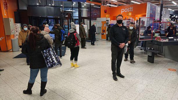 Helsingin Herttoniemen K-supermarket Hertan postipisteen jono perjantaina klo 14.30. Kauppias Markus Ranteen (mies mustissa, vas.) mukaan jonossa oli noin parikymmentä asiakasta.