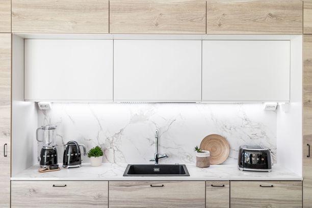 Villiä puukuosia ja Dekton-taso jatkuu myös välitilaan. Musta allas ja mustat keittiökoneet tuovat  kontrastia.