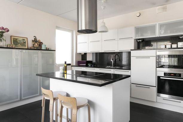 Keittiöön on valittu mustat kivitasot ja valkoiset kaapistot. Valkoinen keittiö on varmasti suomalaisten suosikki.