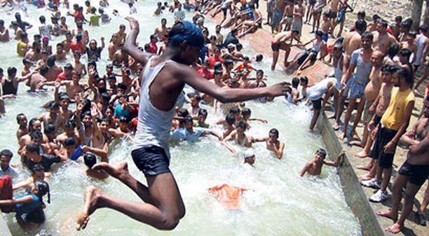 POIS ALTA! Sadat ihmiset hyppäsivät spontaanisti kylpemään jokeen Amritsarissa, Intiassa, kun lämpötila kohosi yli 45 asteen eikä vilvoittavista monsuunisateista ollut vielä tietoakaan.