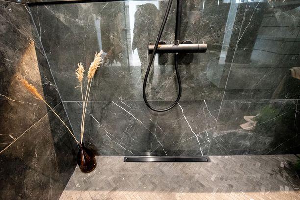 Tässä kylpyhuoneessa oli yhdistelty rohkeasti erilaisia laattoja. Huomaa lattiakaivo seinän vierustalla.