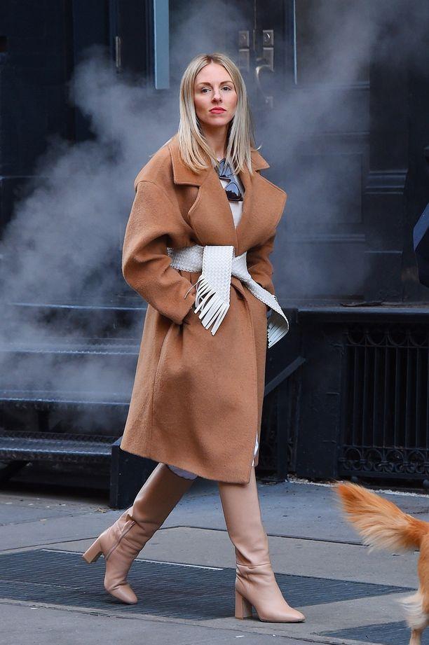 Hienostuneimmat saappaat koskaan? Muotivaikuttaja Shea Marie yhdistää hiekan sävyiset nahkasaappaat valkoisiin housuihin ja beigeen takkiin.