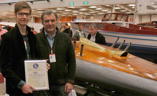 Upean klassikkoveneen omistajat Jani ja Esko Vahto vastaanottivat K-merkin Sikari-veneelle Venemessuilla lauantaina. Taustalla klassikko itse.
