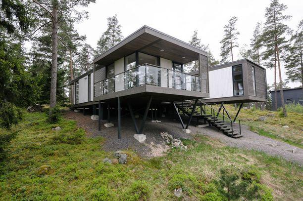 Tämä moderni talo sijaitsee saaristomaisemissa Raaseporissa. Talon suurista ikkunoista näkyy metsämaisemaa.