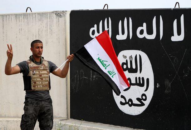 Irakin hallituksen joukkojen sotilas heilutti maan lippua isis-julistuksen edessä Tikritissä keskiviikkona.