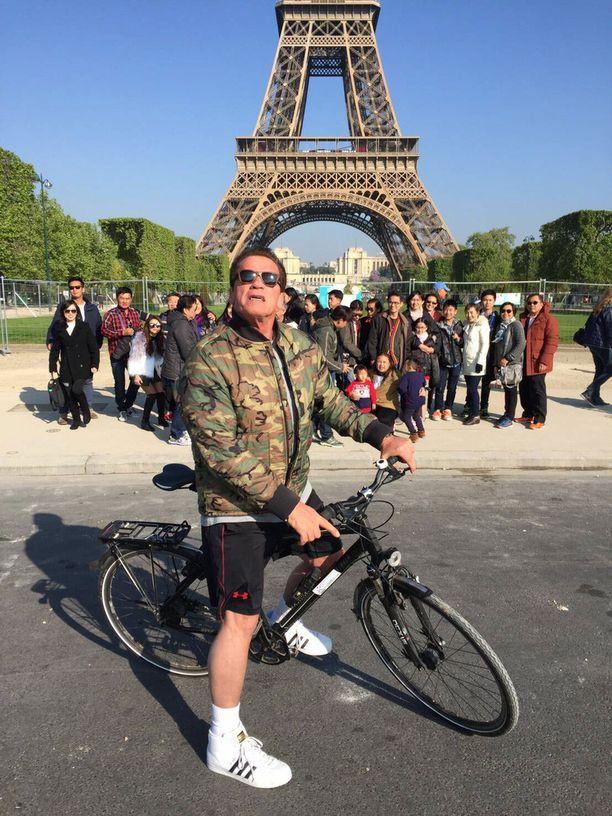 Arnold Schwarzenegger patsasteli kaikessa rauhassa Eiffel-tornin edessä.