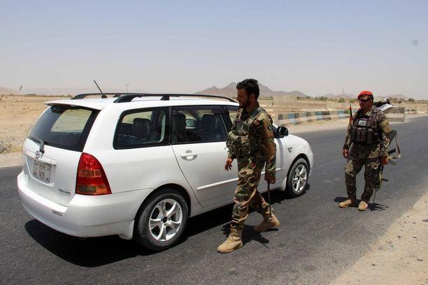 Afganistanin armeijan sotilaat tutkivat autoja Maiwindin alueelle Kandahariin johtavalla tiellä torstaina.