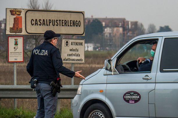 Poliisi informoi Casalpusterlengon pikkukaupunkiin saapuvaa autoilijaa koronaviruseristyksestä.