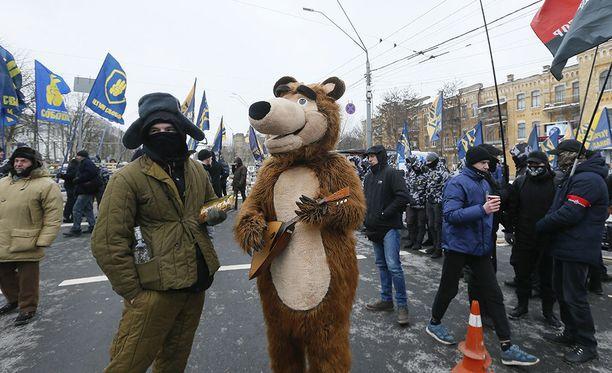 Venäläiseksi karhuksi ja sotilaaksi pukeutuneet aktivistit Venäjän suurlähetystön edessä Kiovassa sunnuntaina. Mielenosoittajat boikotoivat Venäjän presidentinvaaleja.