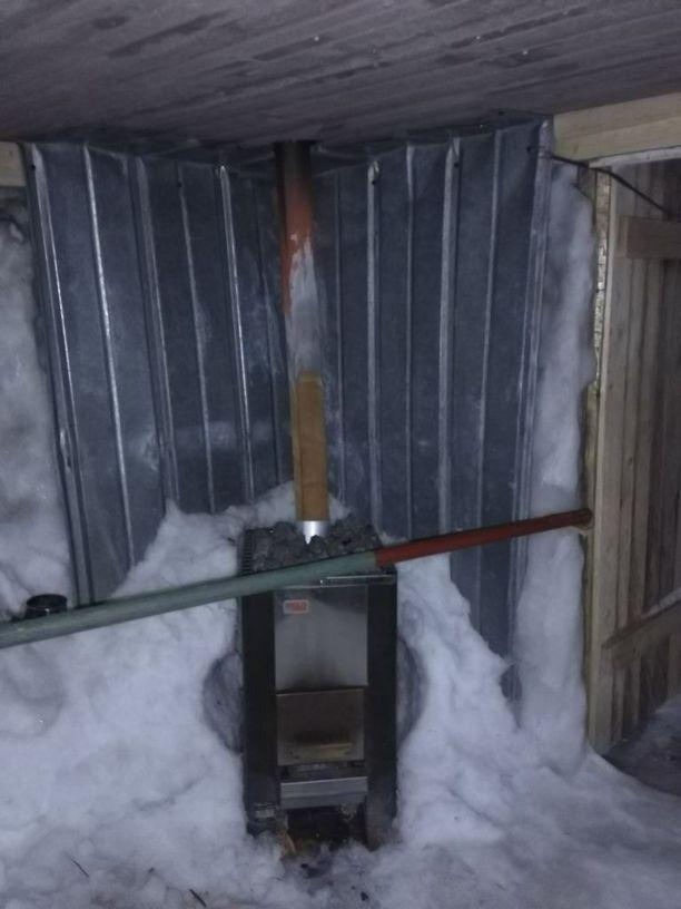 Saunan pitää lämpimänä perinteinen puukiuas.