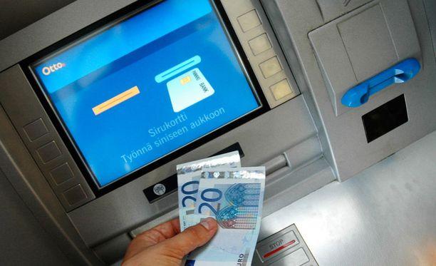 Miehet pyrkivät harhauttamaan naista pankkiautomaatilla.