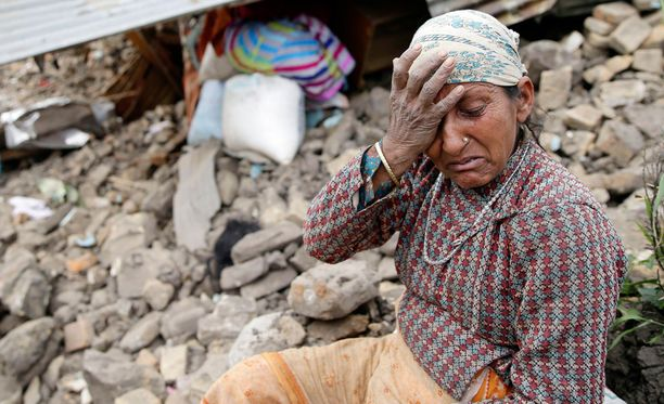 Nainen suri Kumalpurin kylässä tuhoutuneen kotitalonsa edustalla 10-vuotiasta tyttöä, joka kuoli maanjäristyksen seurauksena. Tytön tummaa tukkaa näkyy naisen taustalla raunioissa.