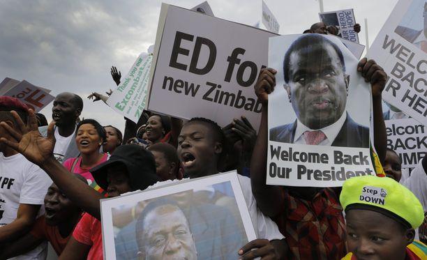 Riemuitsevat ihmiset toivottavat tulevan presidentin tervetulleeksi.